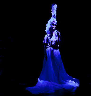 A woman stands with a microphone to her mouth, wearing a feather head dress and long skirt, under a purple spotlight.