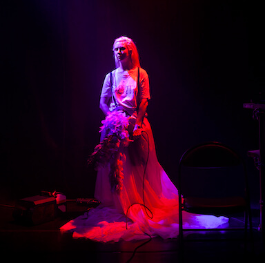 A woman stands angled to the side under a bright pink spotlight, holding a head dress in her hands and wearing a long skirt.