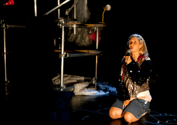 A woman kneeling on the floor, with a microphone to her mouth looking up to the audience.
