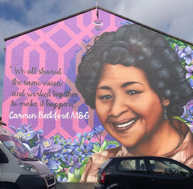 A graffiti image of a woman on the side of a house with a patterned and flowery background