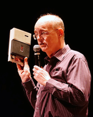 A man holding a tape recorder and microphone, looking away from the camera.