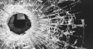 Image of a gun shot shattering glass.