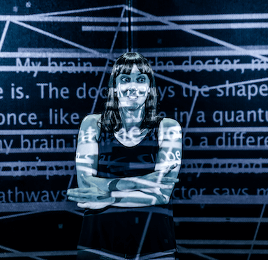 A woman with her arms crossed, with projected shapes, patterns and words appearing over her face and body.