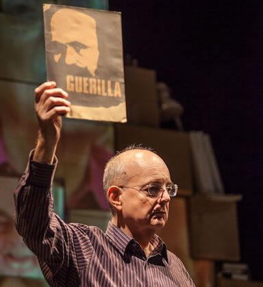 A man performing on stage, holding up a Guerrilla poster up in the air, not looking directly at the camera