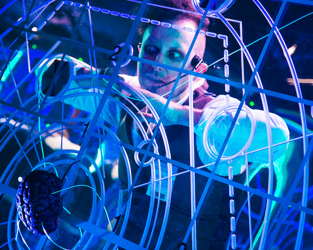 A man performing behind a perspex glass, with overlapping lines.