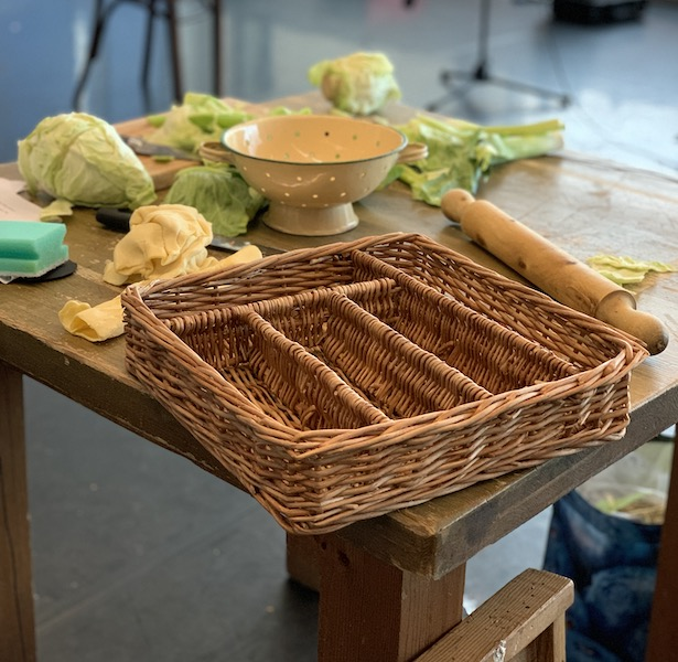 A wooden table scattered with vegetables, a wicker basket and rolling pin.