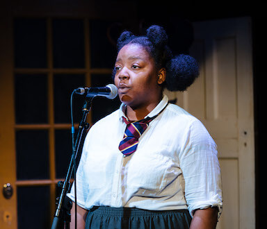 A young woman dressed in a school uniform singing into a microphone on a stand. Two door panels can be seen behind her.