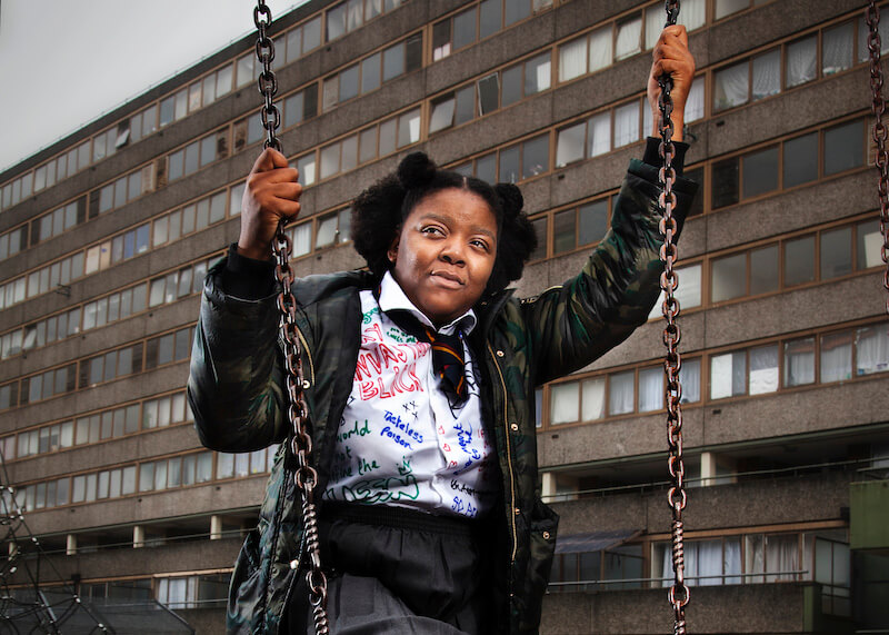 A young woman dressed in a school uniform, holding onto a swing, and looking away from the camera.