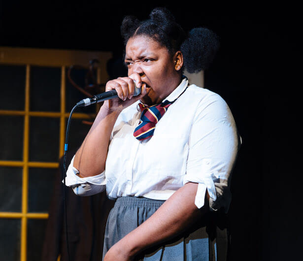 A young woman dressed in a school uniform holding a microphone to her mouth singing.