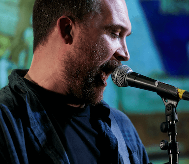A close up image of a man singing into a microphone.