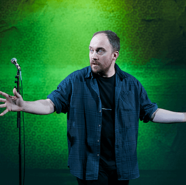 A man looking off to the right with his hands out either side, in front of a projected green back drop.