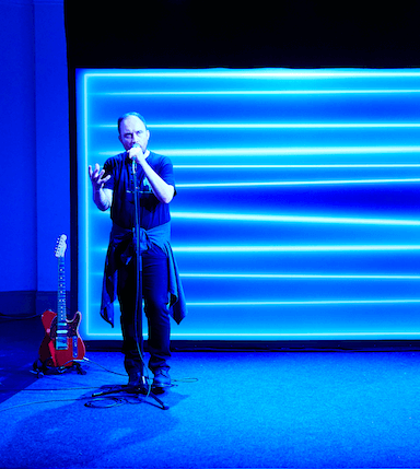 A man singing into a microphone with bright blue lines projected on to a screen behind him.
