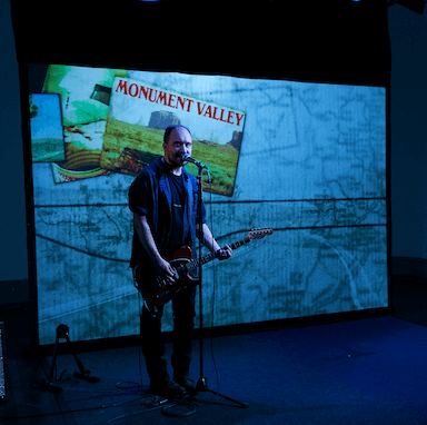 A man singing into a microphone and playing a guitar, standing against a projected image of a map.