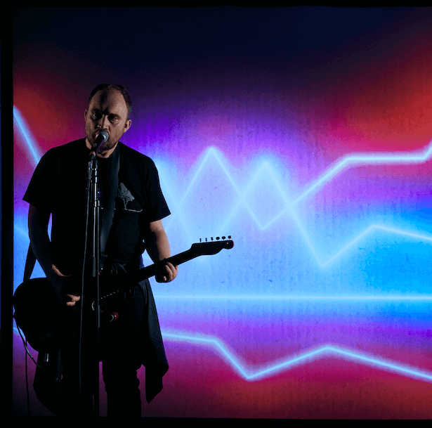 A man singing into a microphone and playing the guitar, with sound waves projected behind him.