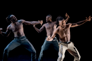 Three men dancing with their arms stretched out and tilted to one side.