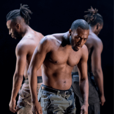 Three men standing back to back, slightly hunched, wearing no top.