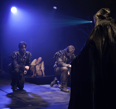 Three men kneeling for a cloaked figure with their back to the camera.