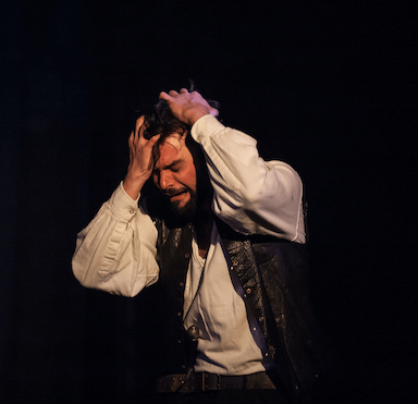 A man in distress holding his hands to his head.