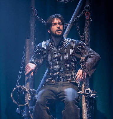 A man sitting in a throne dressed with chains, not looking directly at the camera.