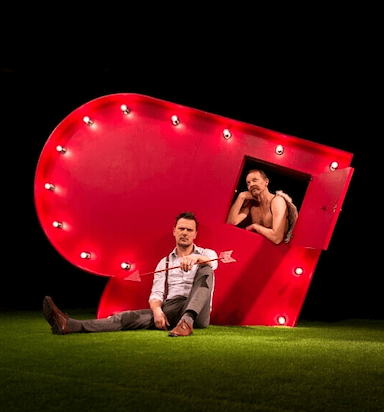 A man sitting on the ground with an arrow in his hand, leaning against a heart shape on its side, another man leans on a window as part of the heart.