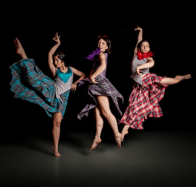 Three women jumping in the air and holding dance poses.