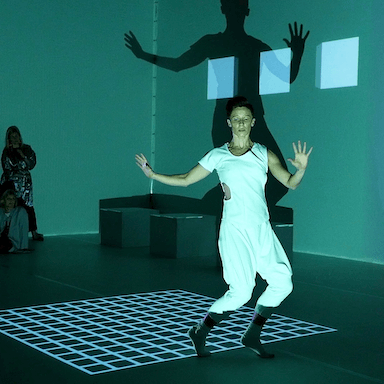 A woman dressed in white, dancing in front of a projected square grid.
