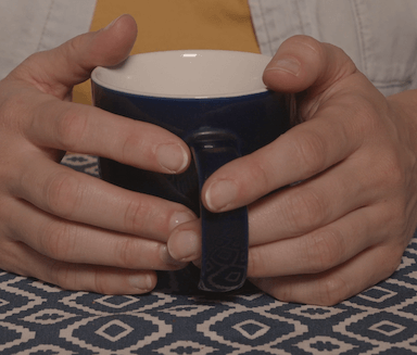 A woman's hands resting gently on a table, clasping a mug
