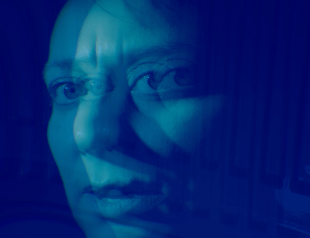 A woman's face looks directly to camera, over a vivid blue background. A mirror image overlaps her face creating a distorted effect.