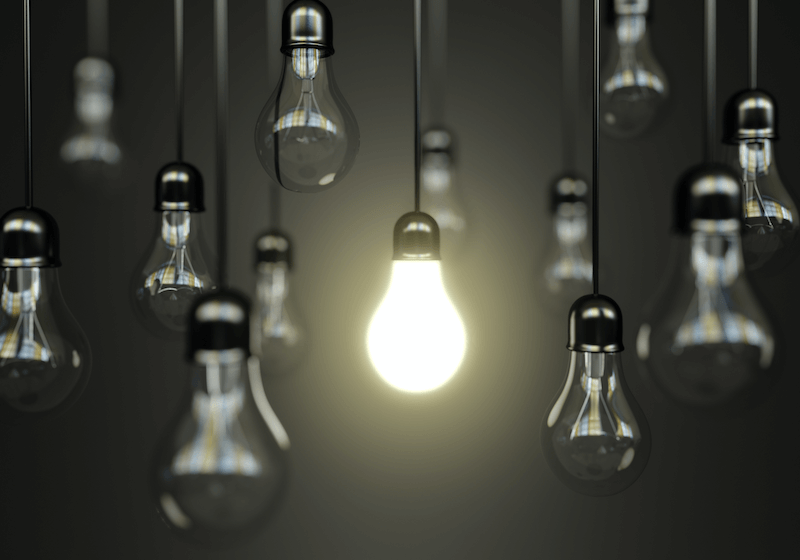 An image of hanging light bulbs, the central one is the only one turned on.
