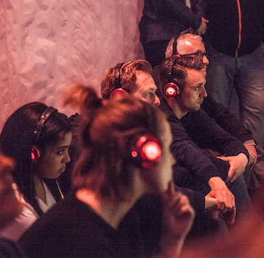 A group of participants wearing headphones, listening and watching something out of shot.