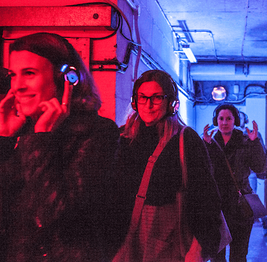 Three women walking behind one another, wearing headphones, the space is lit up red and blue.