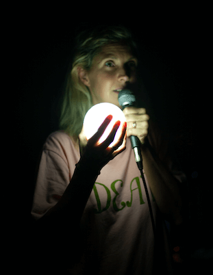 A woman holding a globe and microphone in the dark, the globe lights up her face.