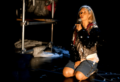 A woman kneeling on the floor, with a microphone to her mouth, looking up to the audience.