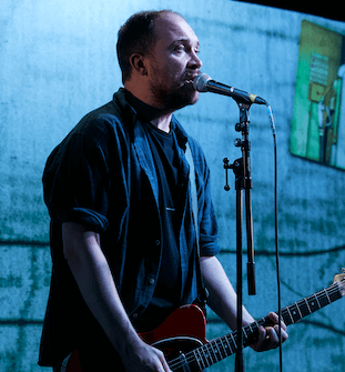 A man singing into a microphone, against a projected backdrop.