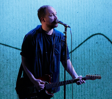 A man singing into a microphone and playing a guitar, against a projected backdrop.