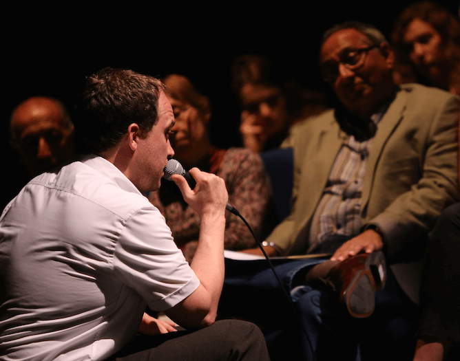 A man speaking into a microphone to an audience who can be seen in their seats.