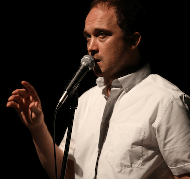 A man speaking into a microphone with his right hand raised slightly.