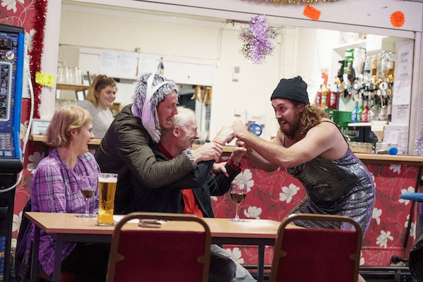 Two men in costume pretending to play fight with another man sat down, while two women look on laughing.