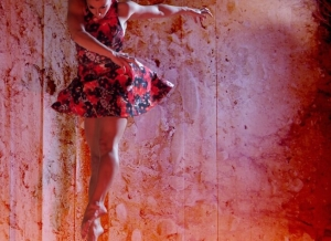 A woman jumping and twisting her body in a dance pose, against a ink splattered projection.