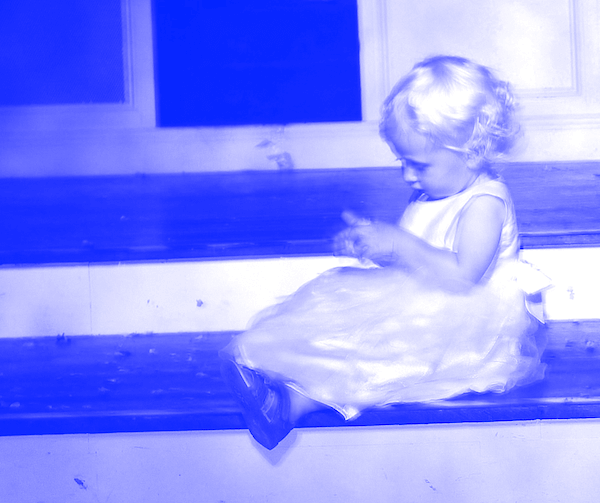 A young child sitting on a step in a party dress, looking at something in her hands. The image has a blue hue.