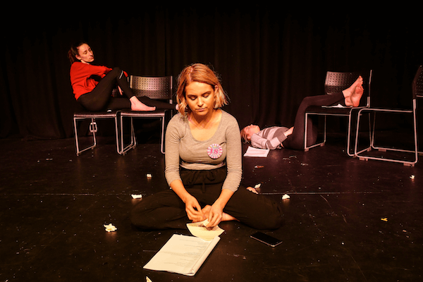 A young woman sitting crossed leg on the floor, two other young women sit and lean against chairs behind her.