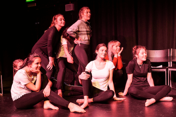 A group of young people performing, some stand, some are sitting on the floor.