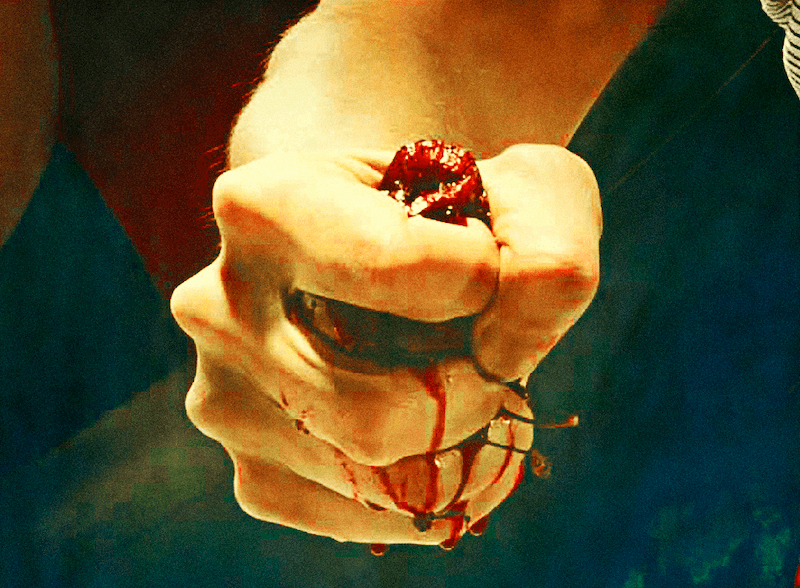 An image of a hand squeezing something, with blood trickling down.