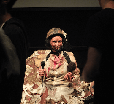 A woman sitting amongst rubbish, she wears a helmet and holds a microphone in her right hand.
