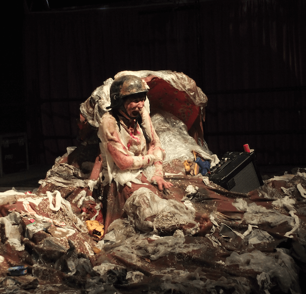 A woman sitting amongst a pile of rubbish, she is wearing a helmet.