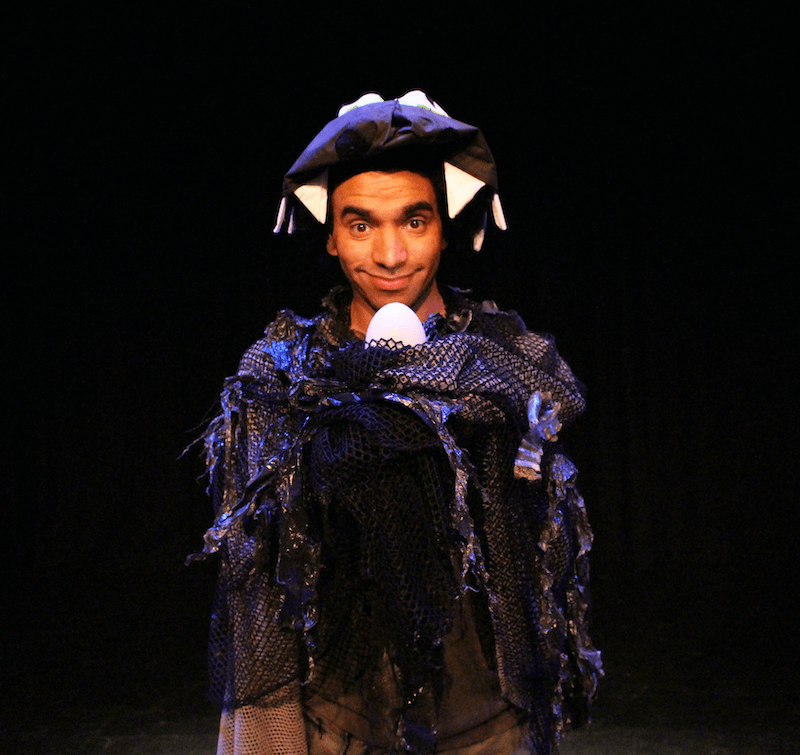 A young man dressed in costume, looking directly at the camera.