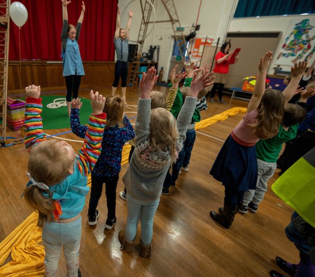 A group of children holding their hands in the air, copying two adults who are doing the same in front of them