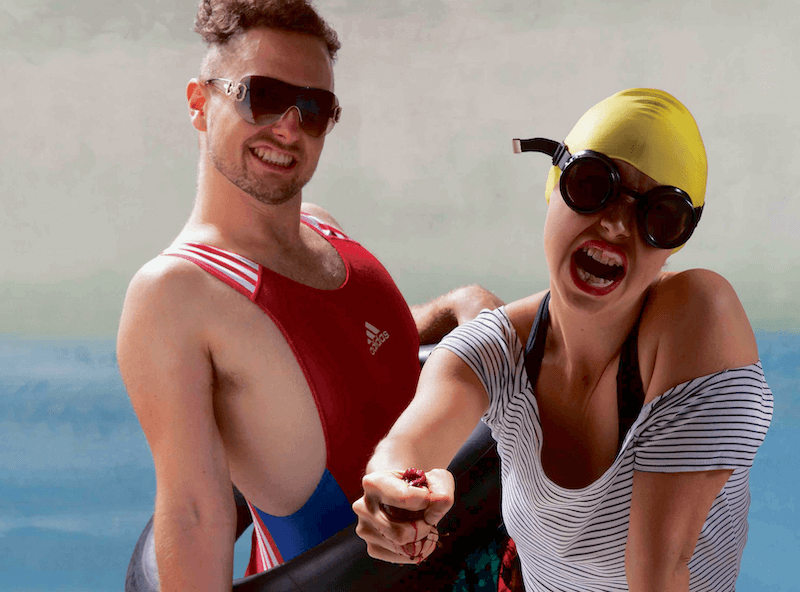 A man in a red swimming costume and sun glasses, next to a woman in a striped top, yellow swimming cap and goggles. She is squeezing something in her hand which is dripping blood.