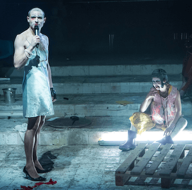 A person wearing a dress and heels, holding a microphone to his mouth. To his left, a woman sits on the step in an empty swimming pool.