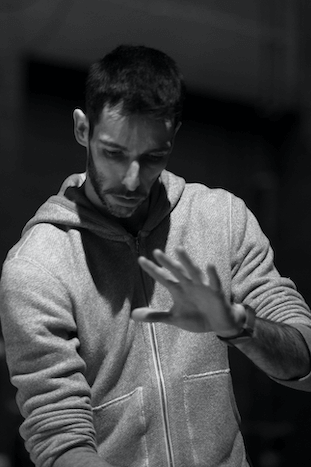 A black and white image of a man looking down with his hands out in front of him.